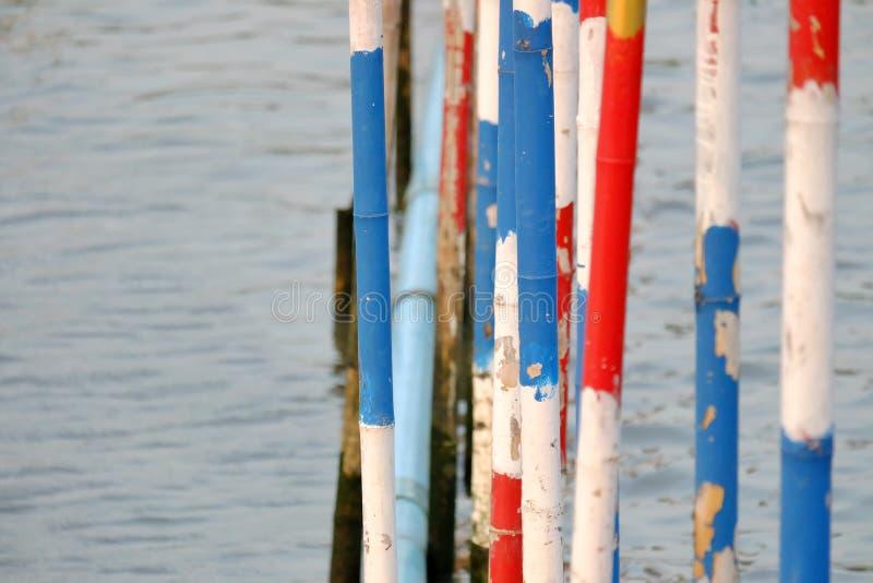 Färgrika bambupoler i floden royaltyfri bild