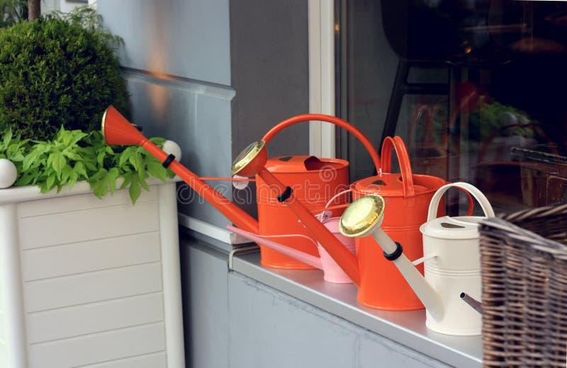 Färgrika bevattna cans på ett shoppafönster royaltyfri fotografi