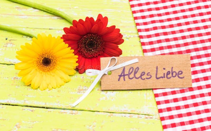Färgrika blommor och kort med tysk text, Alles Liebe, hjälpmedelförälskelse arkivfoton