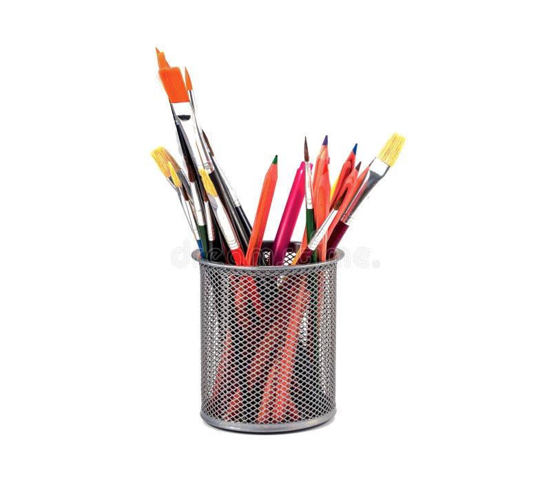 Färgrika blyertspennor och borstar i en kopp arkivfoton