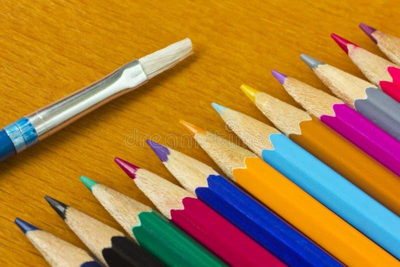 Färgrika blyertspennor och borste royaltyfria bilder