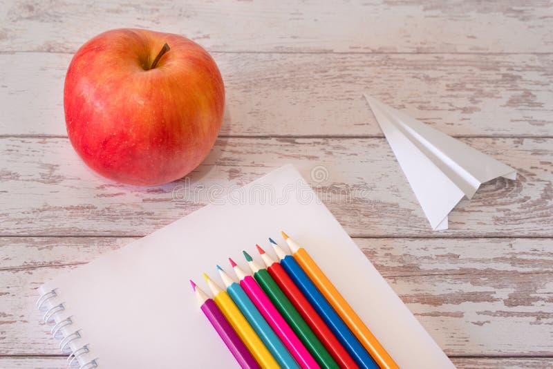 Färgrika blyertspennor på den öppna anteckningsboken och det röda äpplet med pappersflygplanet på ett träskrivbord Begrepp av bör royaltyfria foton