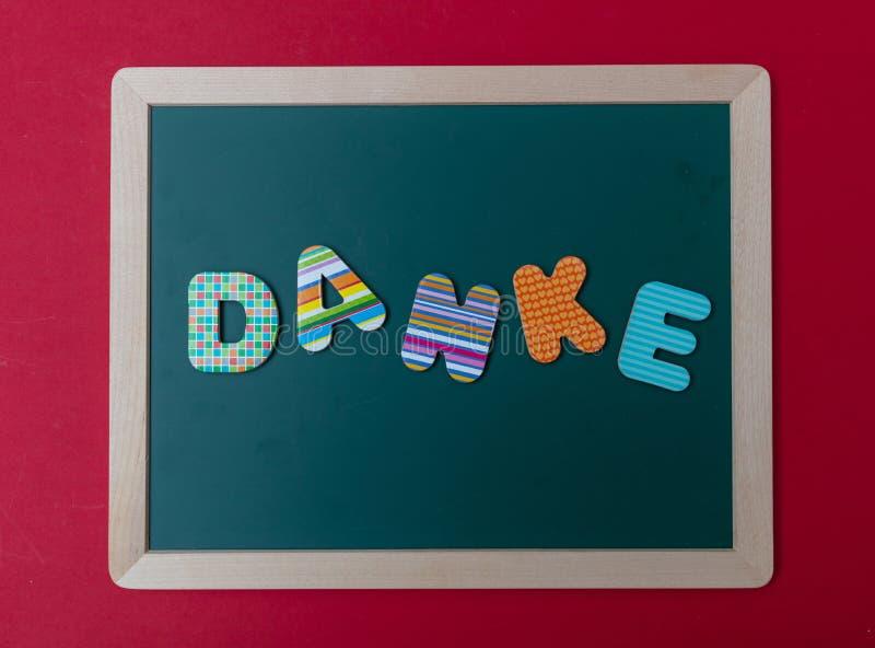 Färgrika bokstäver som formar ordet Danke, tacka dig i tysk, på grönt bräde med träramen, röd väggbakgrund royaltyfria foton