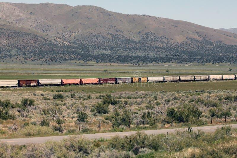 Färgrika boxcars på ett fraktdrev på den höga öknen arkivbild