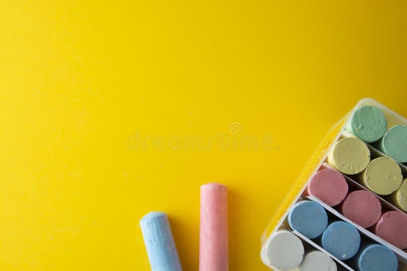 Färgrika chalks över gul bakgrund med kopieringsutrymme för symboler skuggor länge Childhod, affär och design royaltyfri fotografi
