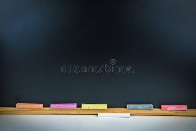 Färgrika chalks och svart tavla royaltyfri fotografi