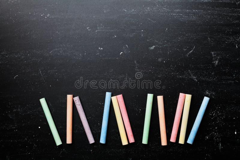 Färgrika chalks på svart tavla för tillbaka till skolabakgrund arkivfoto