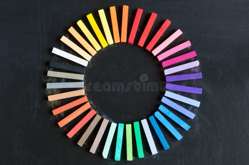 Färgrika chalks ställde upp rundat på cirkel på svart tavlabackgro royaltyfria bilder