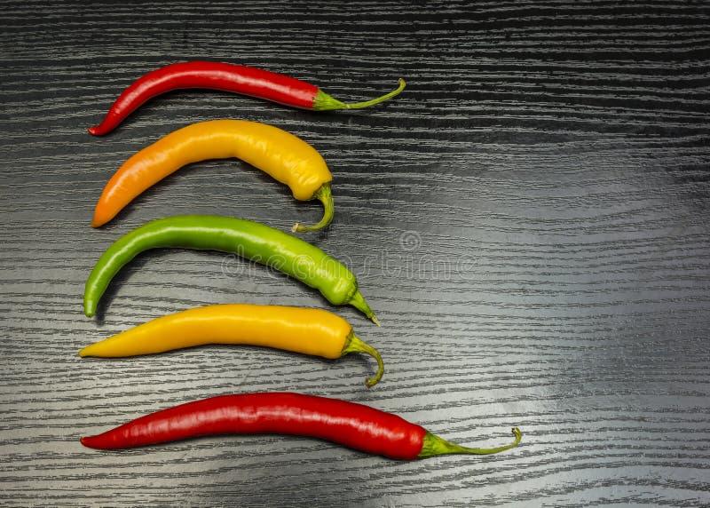 Färgrika chilipeppar på en trätabell arkivbild