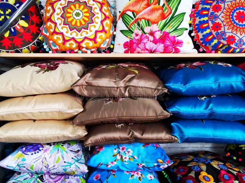 Färgrika dekorativa kuddar på hyllor royaltyfri bild