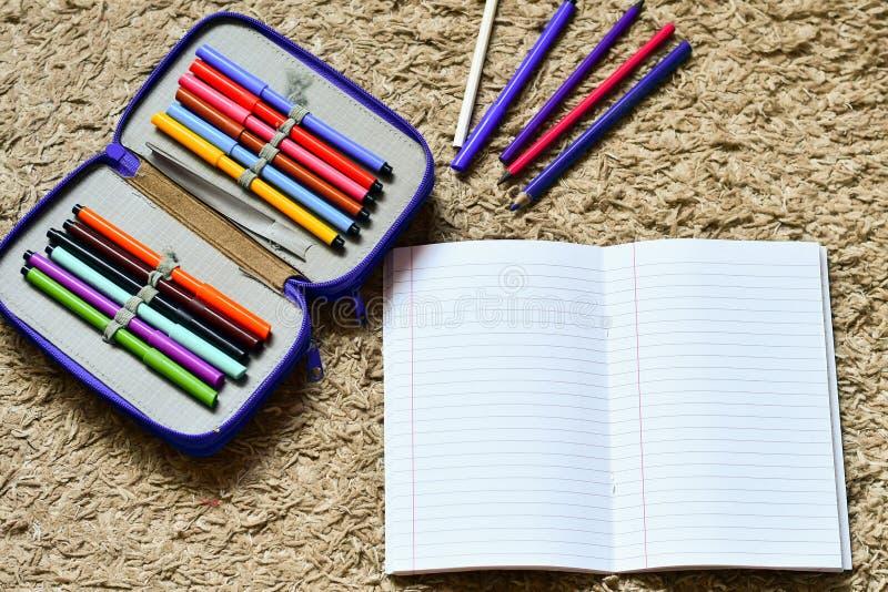 Färgrika dra blyertspennor och öppen epmty anteckningsbok royaltyfria foton