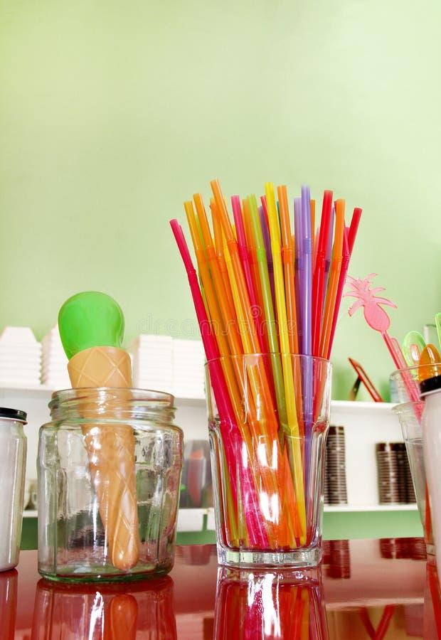 Färgrika dricka sugrör i exponeringsglas, plast- sked och plast-spatel bearbetar kitchenware för glass fotografering för bildbyråer
