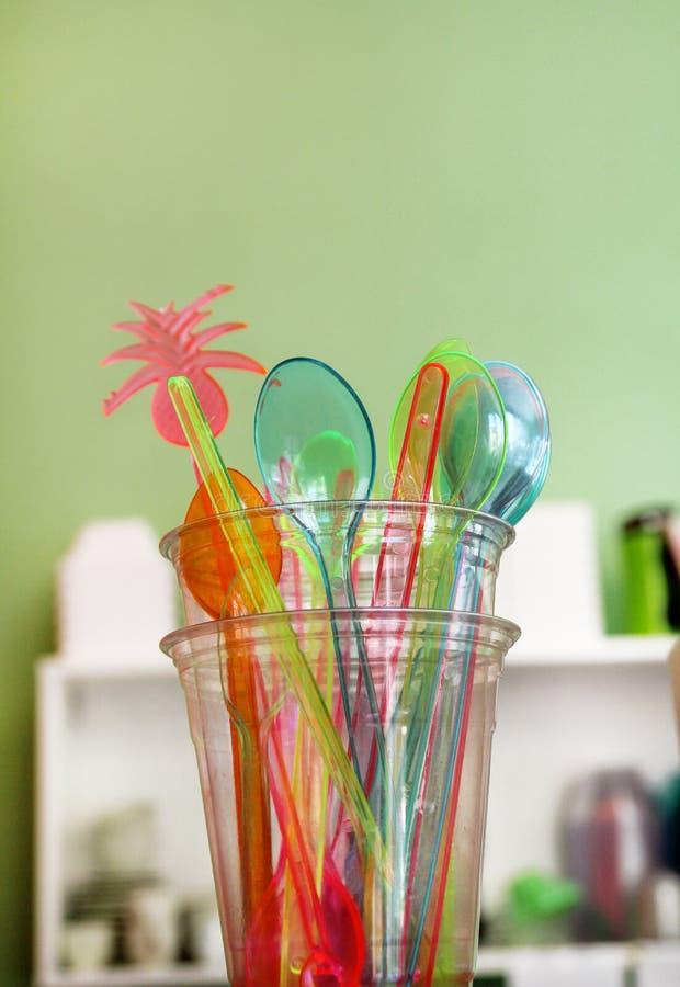 Färgrika dricka sugrör i exponeringsglas, plast- sked och plast-spatel bearbetar kitchenware för glass royaltyfri fotografi