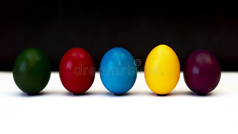 Färgrika easter ägg bredvid de i rad arkivfoton