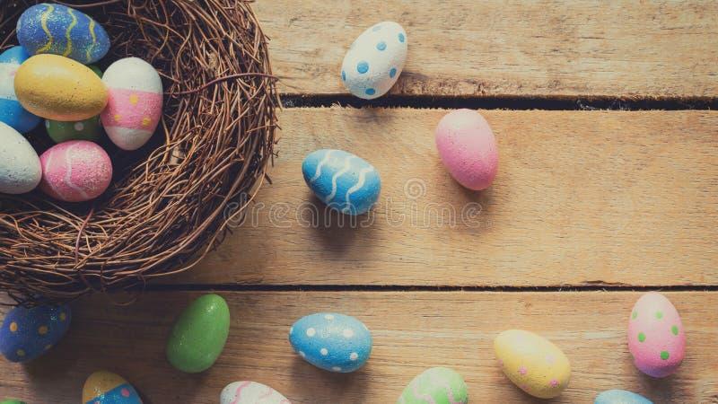 Färgrika easter ägg i propert på plankaträbakgrund med utrymme arkivfoton