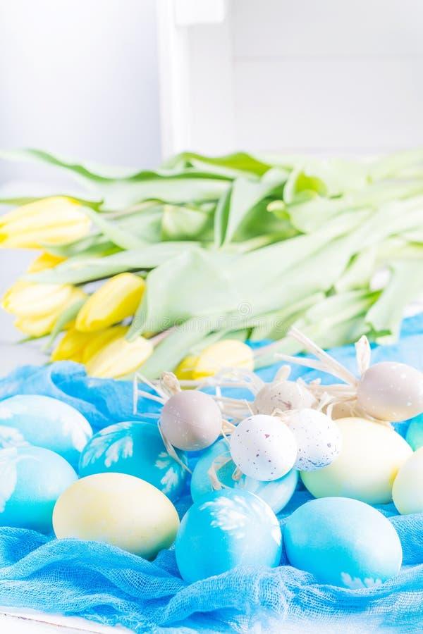 Färgrika easter ägg och tulpan på vitt lantligt wdooen tabellen arkivfoto