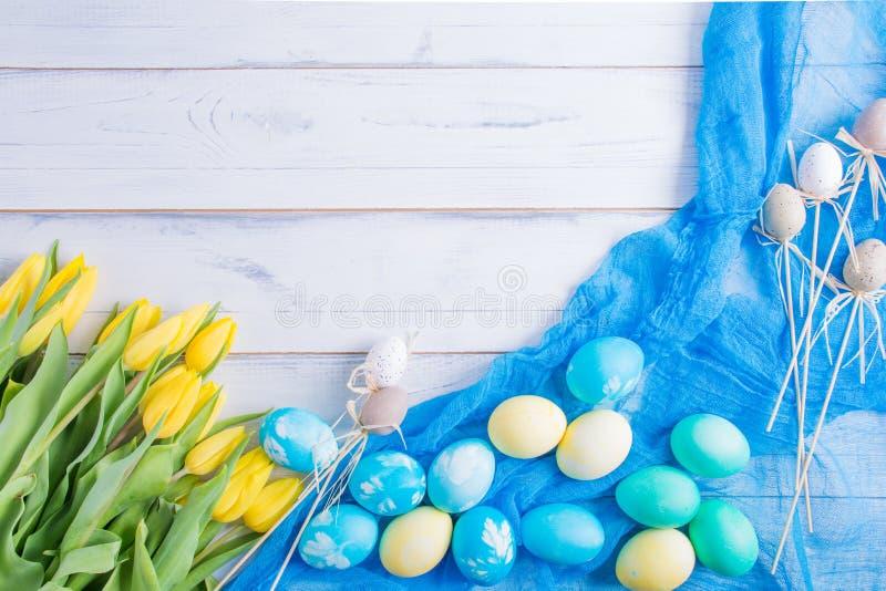 Färgrika easter ägg och tulpan på vitt lantligt wdooen tabellen royaltyfria bilder