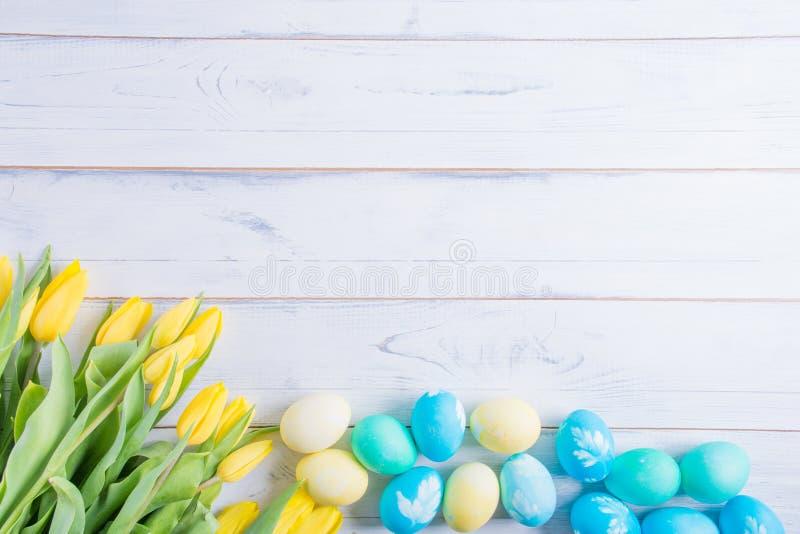Färgrika easter ägg och tulpan på vitt lantligt wdooen tabellen fotografering för bildbyråer