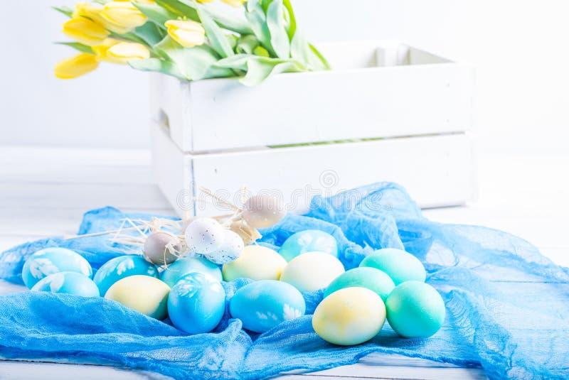 Färgrika easter ägg och tulpan på vitt lantligt wdooen tabellen royaltyfri foto
