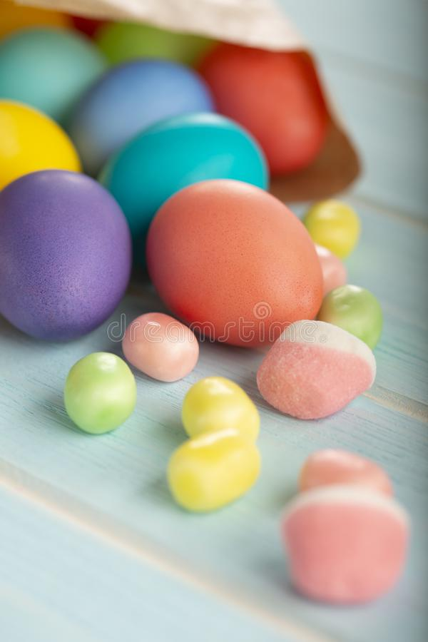 Färgrika färgade fega ägg för påsk i en pappers- påse och sötsaker royaltyfria bilder