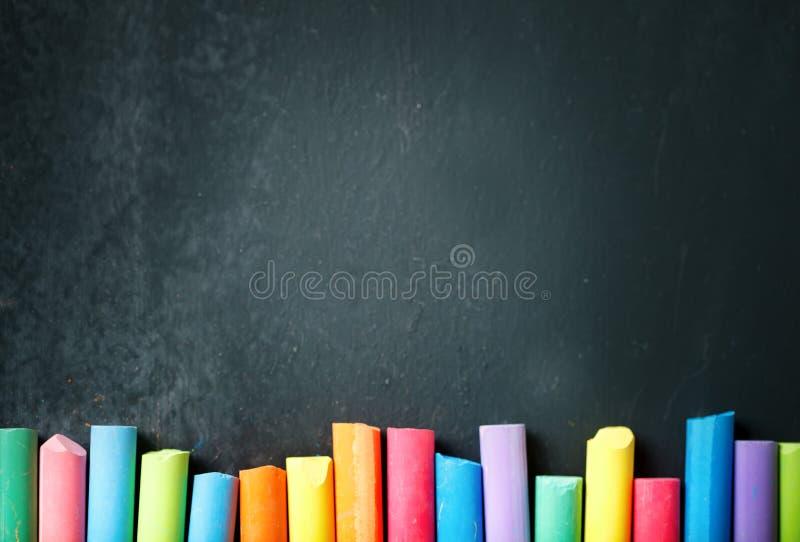 Färgrika färgpennor på svart tavla som drar tillbaka bakgrundsskola till arkivfoto