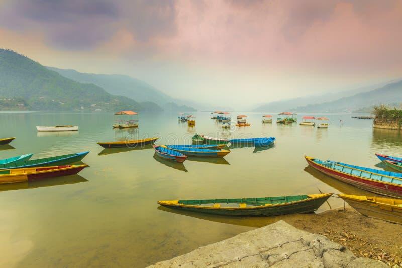 Färgrika fartyg som parkeras i Phewa väntande på turister och bakgrund för sjö på solnedgång fotografering för bildbyråer