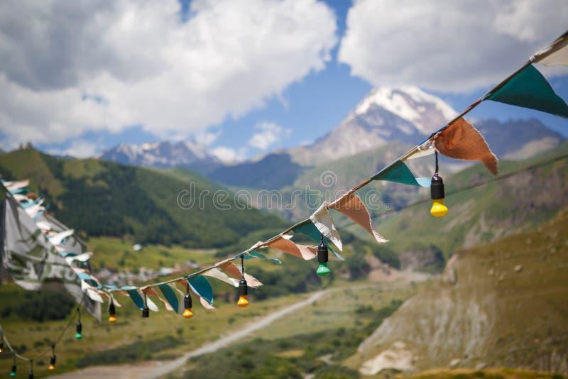 Färgrika flaggor, girlander av ljusa kulor och en hängmatta på bakgrunden av en bergdal som förbiser överkanten av Kazbegi arkivbilder