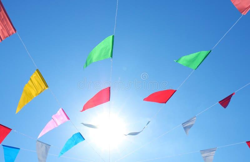 Färgrika flaggor på himmel- och solljusbakgrunden, flaggor fodrar den utsmyckade färgrika flaggalinjen och vindhimmel, festivalfl fotografering för bildbyråer