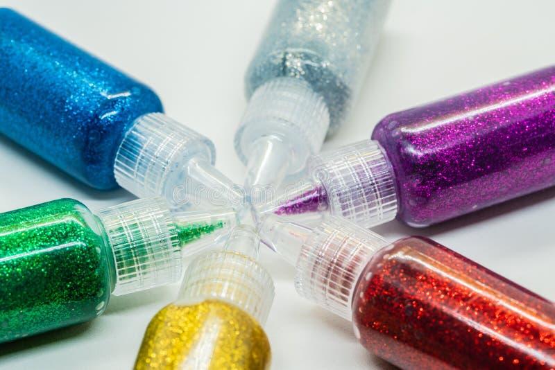 Färgrika flaskor som fylls med, blänker lim arkivbilder