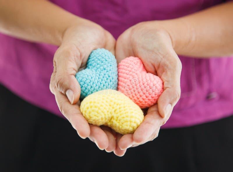 Färgrika flerfärgade sticka hjärtor för selektiv fokus som rymms av kvinnligs båda händer som föreställer portionhänder, service, royaltyfri bild