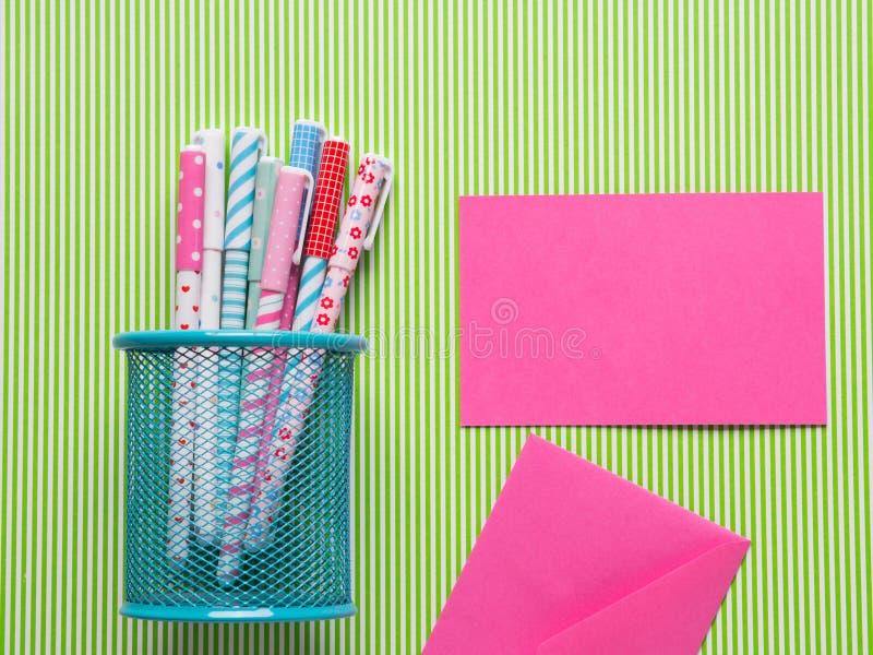 Färgrika flickaktiga pennor på grön bakgrund med kortet fotografering för bildbyråer