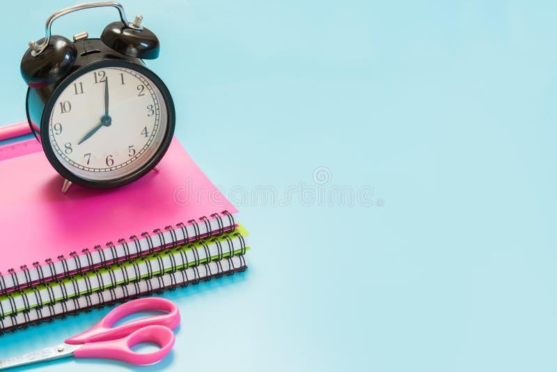 Färgrika flickaktiga skolatillförsel, bok och ringklocka på punchy blått close upp tillbaka skola till royaltyfri bild