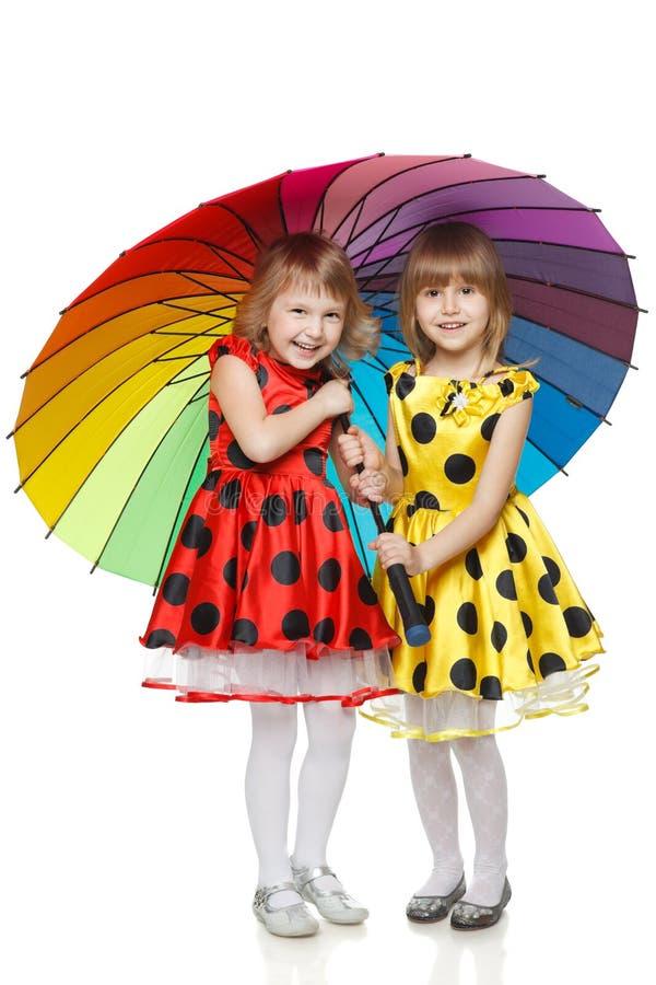 färgrika flickor som under plattforer paraplyet fotografering för bildbyråer