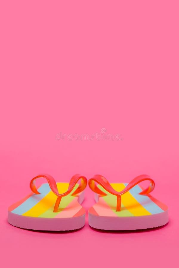 Färgrika Flip Flops på rosa bakgrund arkivbild
