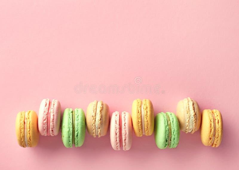 Färgrika franska macarons på rosa bakgrund fotografering för bildbyråer