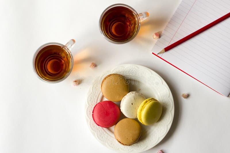 Färgrika franska makron med två kopp te på den lekmanna- vitlägenheten arkivbild
