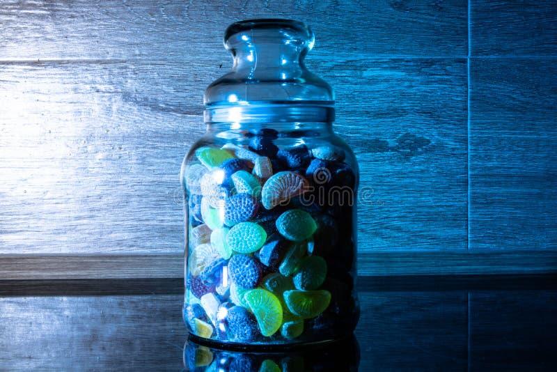 Färgrika fruktgodisar i genomskinligt exponeringsglas royaltyfria foton
