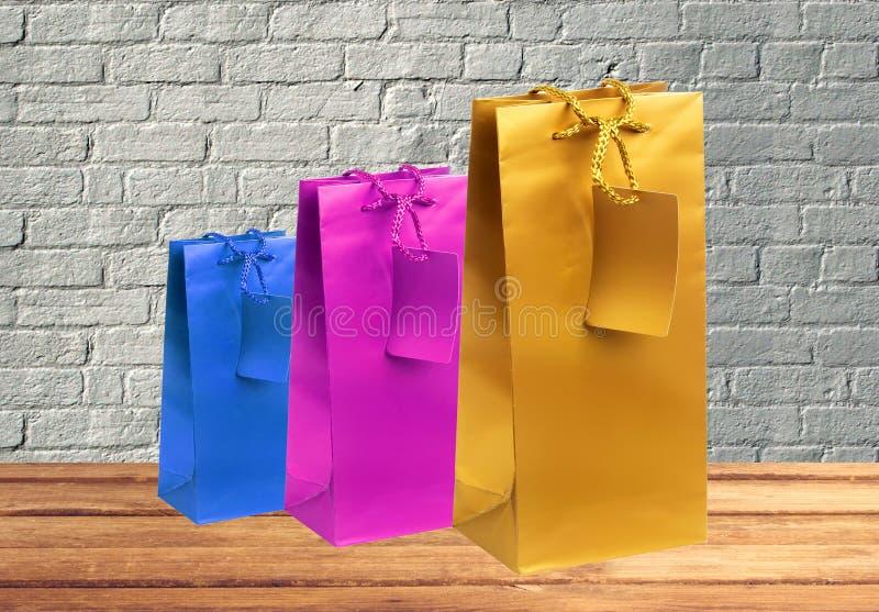 Färgrika gåvashoppingpåsar på trätabellen över tegelstenväggen arkivfoton