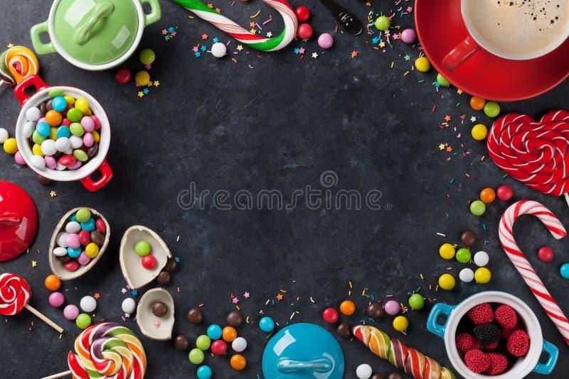 Färgrika godisar och kaffekoppram arkivfoto