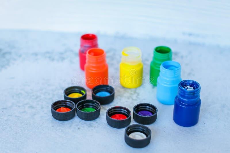 Färgrika gouache- eller akrylmålarfärger i krus på vit grungebakgrund, selektiv fokus arkivfoton
