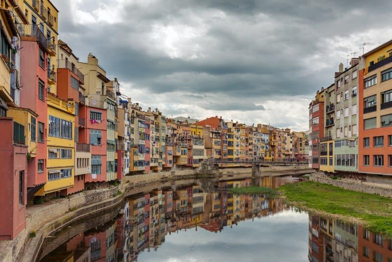 Färgrika gula, röda och orange hus med de Catalan flaggorna reflekterade i vattenfloden Onyar, i Girona royaltyfri foto