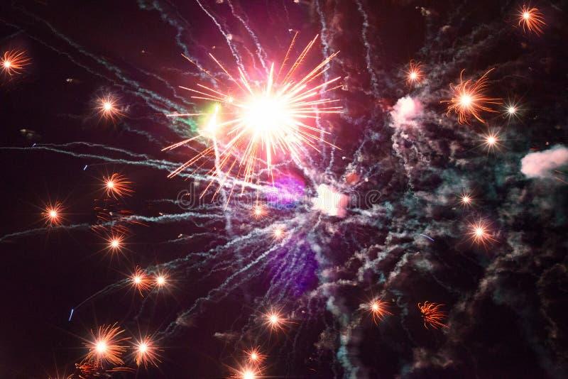 Färgrika guld- rosa purpurfärgade fyrverkeriljus i natthimmel, avläste glidbanafilmtappning royaltyfri foto
