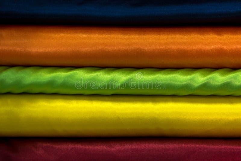 Färgrika härliga tyger som staplas i en hög arkivbilder