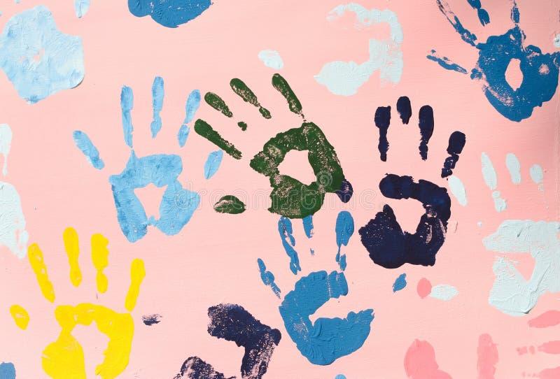 Färgrika handtryck på den rosa väggen royaltyfri bild
