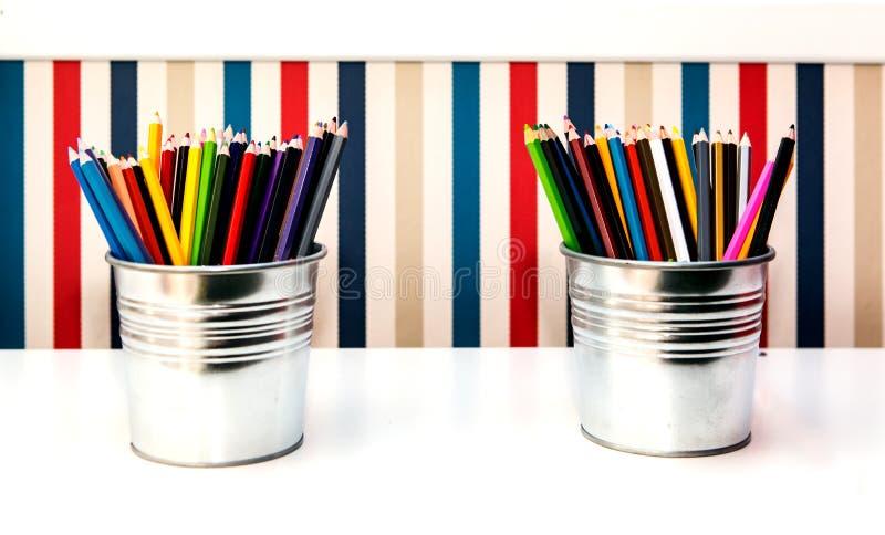 Färgrika hinkar för blyertspennor itu på bakgrund arkivbild