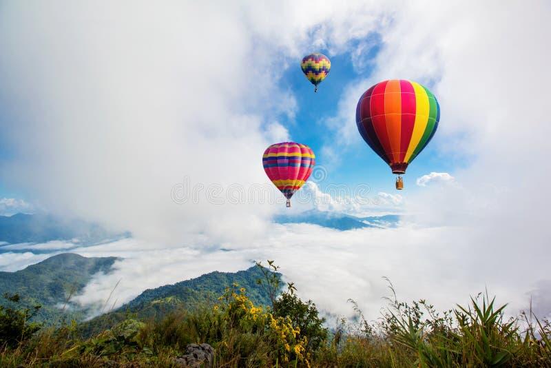 Färgrika hot-air ballonger som flyger över berg fotografering för bildbyråer