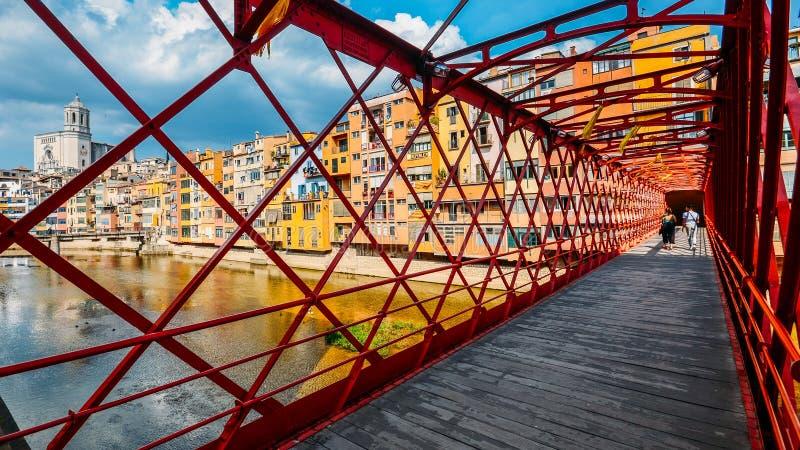 Färgrika hus som igenom ses den röda järnbron i Girona, Catalonia, Spanien fotografering för bildbyråer