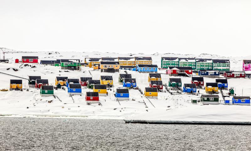 Färgrika inuithus på snökullen, Aasiaat stad fotografering för bildbyråer