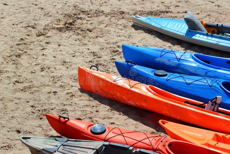 Färgrika kajaker och kanoter på den sandiga stranden arkivbilder