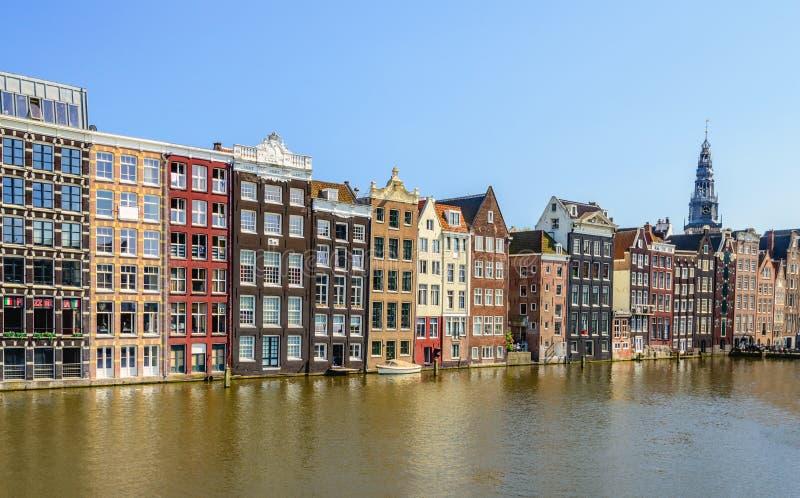 Färgrika kanalhus på Damraken i den holländska huvudAmsterden arkivbild